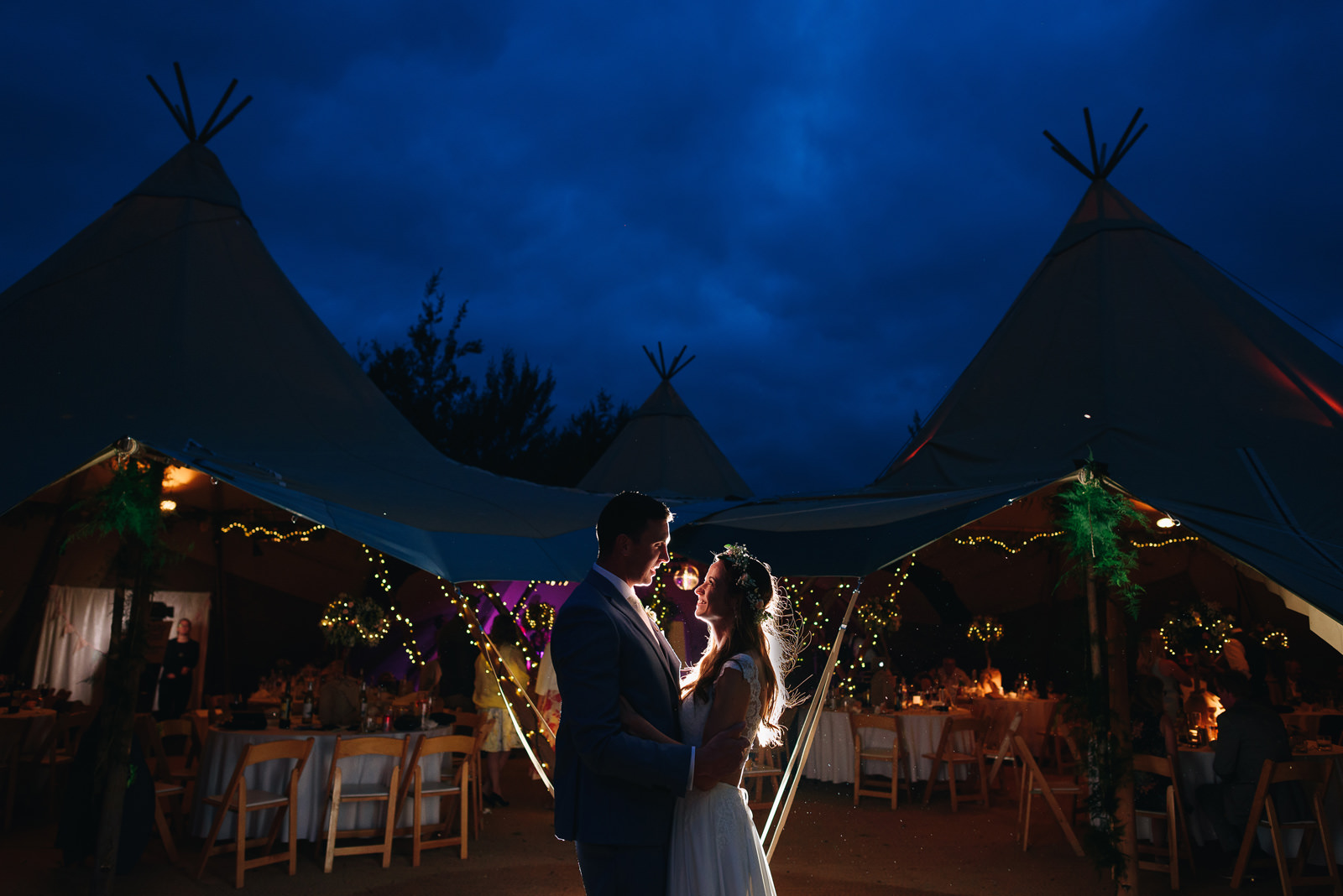 amazing night time wedding portrait in front of a tipi
