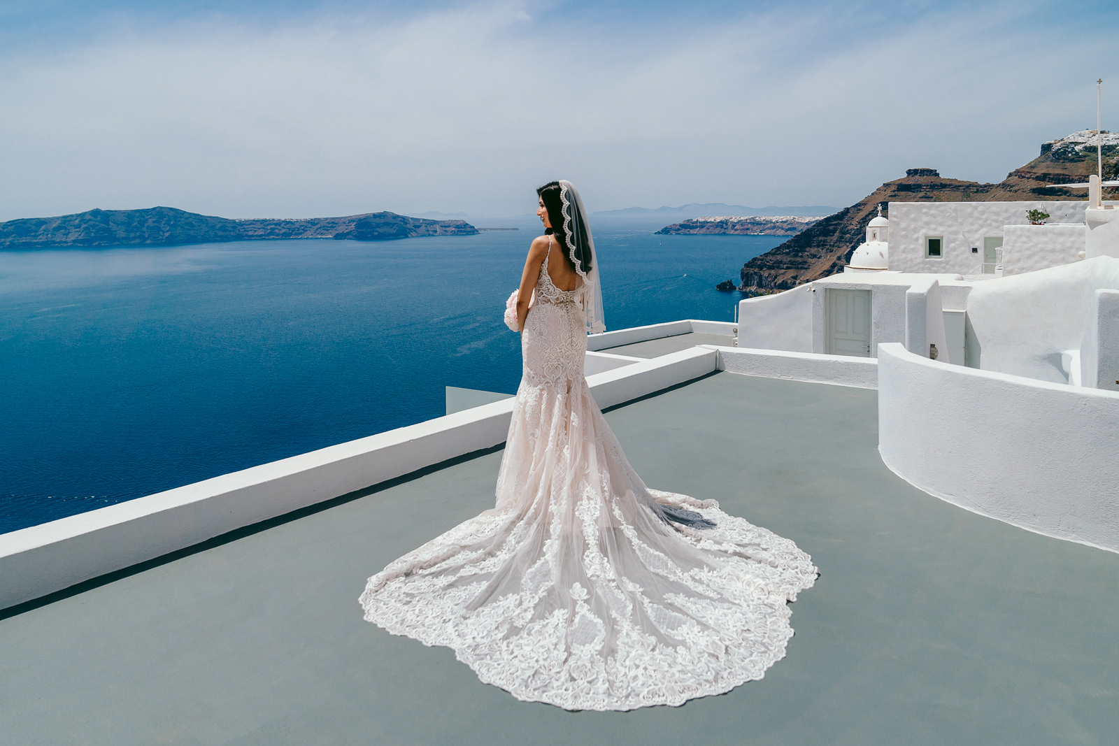 Santorini Wedding Photographer takes a rooftop photo of the brid