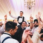 groom being lifted on shoulders of partying wedding guests