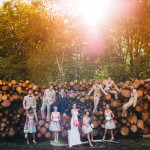 cool bridal party photograph standing on a pile of logs