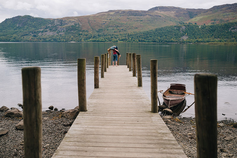 couple on pier with lake and mountains in background