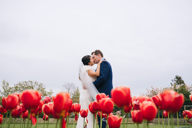 couple kissing surrounded by red flowers at bristol zoo gardens
