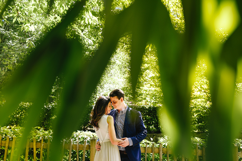 Romantic and beautiful portrait of couple in love shot through palm leaves