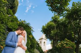 the couple embrace in the gardens with an old clock tower in the background