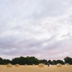 twia winner bride and groom running through hay bales in a cornfield