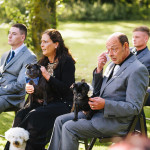 father of bride crying as pug with a bow sits on his lap